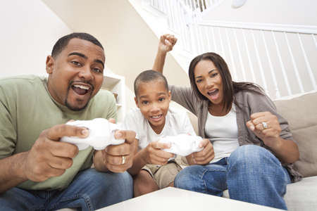 African American family, parents and son, having fun playing computer console games together, Father and son have the handset controllers and the mother is cheering the players. photo