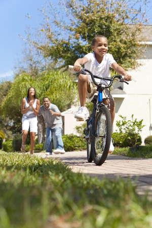 Una joven familia afroamericana con ni�o chico montar su bicicleta y sus padres emocionados felices dando aliento detr�s de �l Foto de archivo