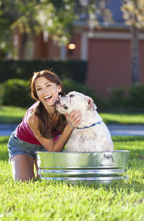 badning: A beautiful young woman being licked by her pet dog, a bulldog, while washing him outside in a metal tub
