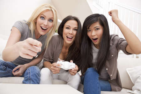 Three beautiful interracial young women friends at home having fun playing computer games together and laughing photo