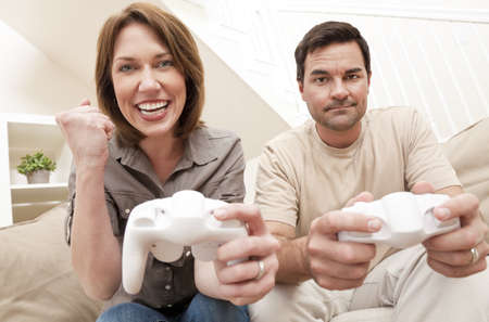 sexes: Man and woman married couple having fun playing computer console game together, the woman is celebrating winning the man is upset losing