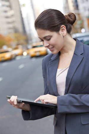 A happy young woman using her tablet computer outside in an American city with yellow taxis behind her. Shot on location in New York City photo