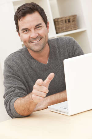 Smiling man in his thirties at home using his laptop computer and pointing to camera Stock Photo - 9247040