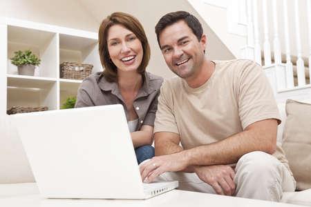 Feliz pareja hombre y mujer en sus treintas, sentados juntos en casa en un sof� en un equipo port�til