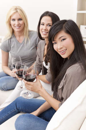Interracial group of three beautiful young women friends at home drinking red wine together Stock Photo - 9247095