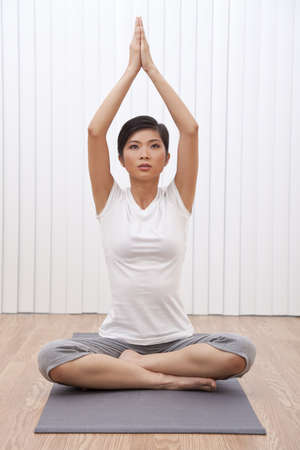 A beautiful young Chinese Asian Oriental woman sitting cross legged in a yoga position at a gym photo