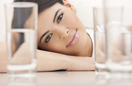 Studio portrait of a beautiful young Latina Hispanic young woman or girl looking thoughtful resting on her hands looking through glasses of water Stock Photo - 9247097