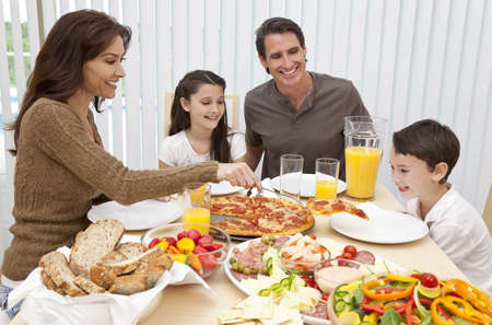 An attractive happy, smiling family of mother, father, son and daughter eating salad and pizza at a dining table, The mother is serving a slice of pizza to the excited boy. Stock Photo