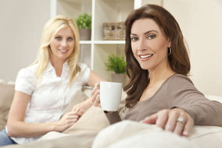 30s: Two beautiful women friends at home drinking tea or coffee together Stock Photo