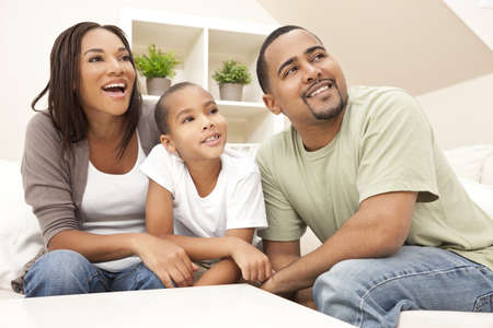 Happy African American family, parents and son, sitting on a sofa at home laughing and smiling photo