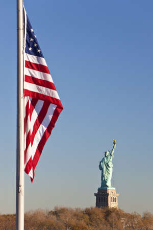 The Statue of Liberty, New York City, United States of America with the Stars and Stripes flag in the foreground photo