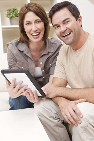 Happy man and woman couple in their thirties, sitting together at home on a sofa using a tablet computer photo