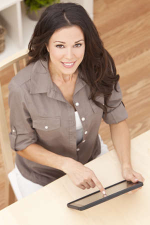 sit: Overhead photograph of a happy beautiful young woman sitting at home using a tablet computer Stock Photo