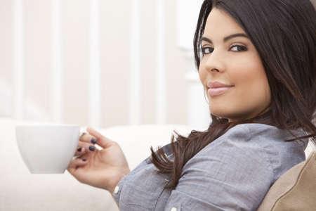 enigmatic: Una bella giovane donna Latina Ispanici o una ragazza con un sorriso enigmatico meraviglioso bere t� o caff� da una tazza bianca