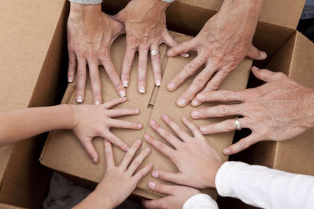 Concept photograph of family hands, parents son and daughter, unpacking a box and moving into a new home. photo