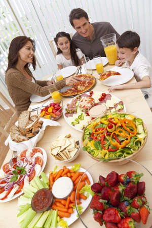 familia comiendo: Una familia feliz y sonriente atractiva de madre, padre, hijo y su hija comiendo ensalada y pizza en una mesa de comedor, la madre está sirviendo una rebanada de pizza al niño emocionado.