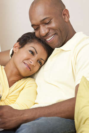 A happy African American man and woman couple in their thirties sitting at home together smiling. Stock Photo - 9312842