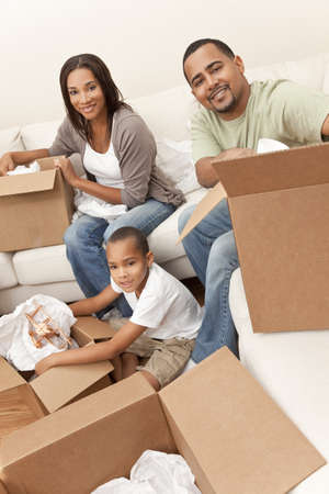 African American family, parents and son, unpacking boxes and moving into a new home, The adults are unpacking crockery and homeware, the child is unpacking a toy airplane. photo