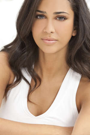 Studio portrait of a beautiful young Latina Hispanic young woman or girl in a white vest top with her arms folded Stock Photo - 9349338