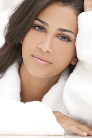 white robe: Portrait of a beautiful healthy young brunette woman in a white spa bath robe Stock Photo
