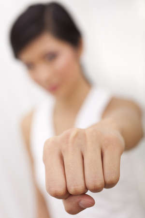 A beautiful Chinese Asian Oriental girl performing a martial arts fist punch to the camera, the focus is on her fist photo