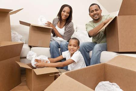 cajas de carton: Familia afroamericana, padres e hijo, desempaquetado cuadros y pasar a un nuevo hogar, que los adultos son desembalaje vajilla, el ni�o es descomprimir un avi�n de juguete.
