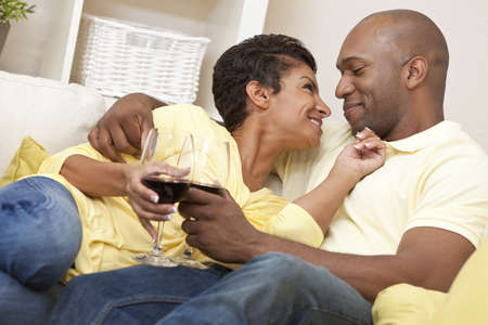 A happy African American man and woman couple in their thirties sitting at home together smiling and drinking glasses of red wine. Stock Photo - 9349337
