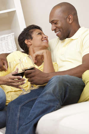 A happy African American man and woman couple in their thirties sitting at home together smiling and drinking glasses of red wine. Stock Photo - 9349333