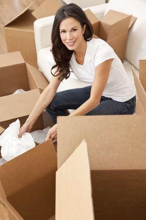Una hermosa sola joven desembalaje de cuadros y pasar a una nueva casa. Foto de archivo