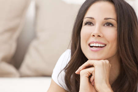 Portrait of a beautiful brunette young woman in t-shirt smiling laying on her sofa at home photo