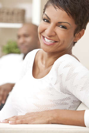 people laughing: A happy African American man and woman couple in their thirties sitting at home, the woman is in focus in the foreground the man out of focus in the background. Stock Photo