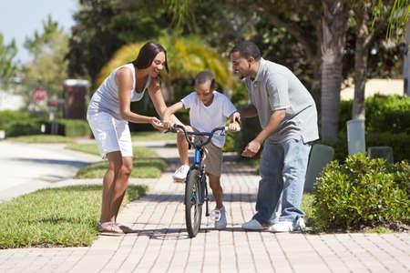 Une jeune famille afro-américaine avec l'enfant garçon sur son vélo et son plaisir des parents ravis en l'encourageant. Banque d'images