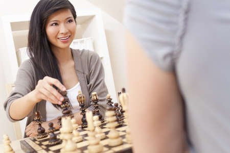toothy: A beautiful young Chinese Asian Oriental woman with a wonderful toothy smile playing chess at home