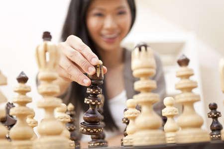 jugando ajedrez: Fotograf�a de enfoque selectivo de hermosa mujer joven de China Oriental asi�tica jugando al ajedrez
