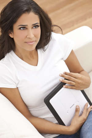 Portrait of a beautiful young Latina Hispanic woman or girl looking thoughtful and using a tablet computer photo