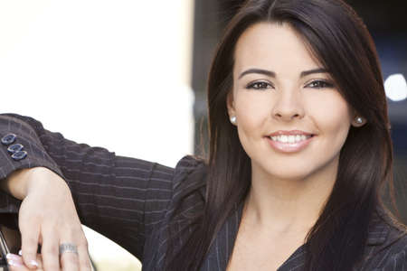 Outdoor portrait of a beautiful young Latina Hispanic woman or businesswoman smiling  photo