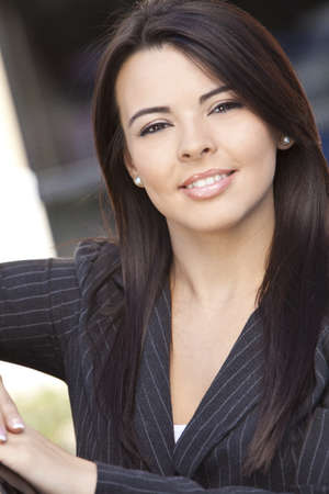 Outdoor portrait of a beautiful young Latina Hispanic woman or businesswoman in a suit smiling  photo
