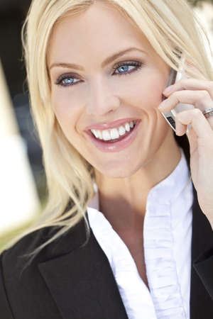 A beautiful young businesswoman smiling and talking on her cell phone Stock Photo - 9360696