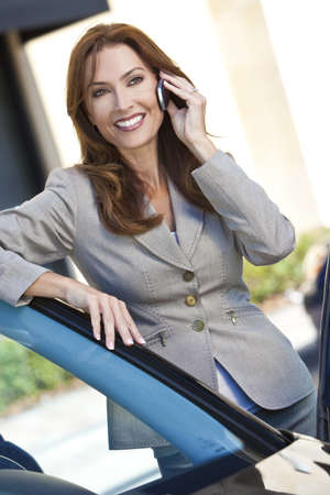cel: Outdoor portrait of a beautiful young brunette woman or businesswoman leaning on her car and talking on a cell phone