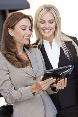 Two happy and smart businesswomen using a tablet computer photo