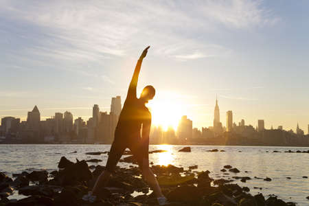 A woman runner stretching in a yoga position in front of the Manhattan skyline, New York City, United States of America, at early morning dawn sunrise photo