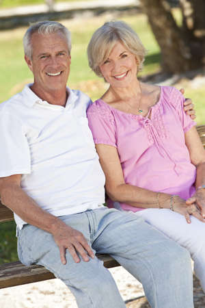 Happy senior man and woman couple sitting together outside in sunshine Stock Photo - 9383937