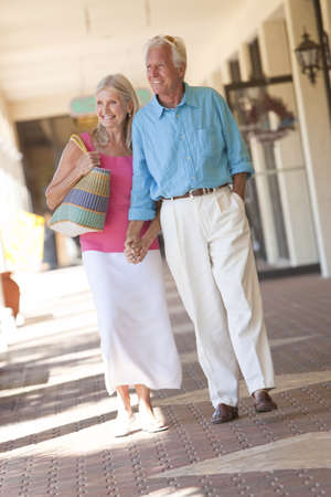 Happy senior man and woman couple holding hands and walking through a sunlit shopping mall Stock Photo