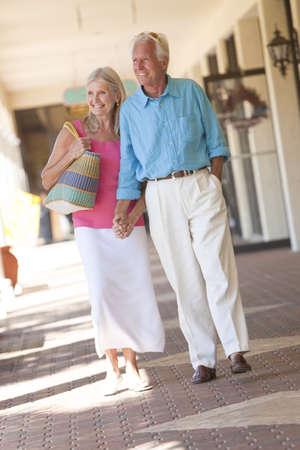 Senior hombre y mujer pareja feliz manos y caminar a trav�s de un centro comercial iluminado
