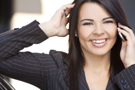 Outdoor portrait of a beautiful smiling young Latina Hispanic woman or businesswoman talking on her cell phone Stock Photo - 9436003