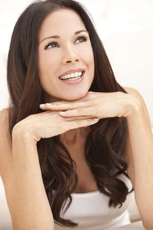 Portrait of a beautiful brunette young woman with perfect teeth smiling and resting on her hands Stock Photo - 9435951