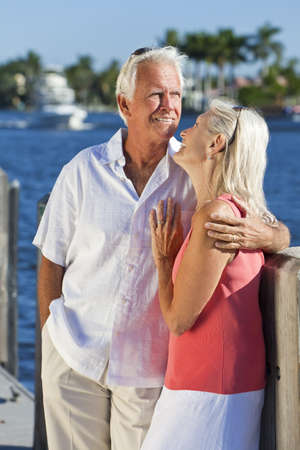 Happy senior man and woman couple together on vacation by the sea in a tropical setting with bright clear blue sky. photo