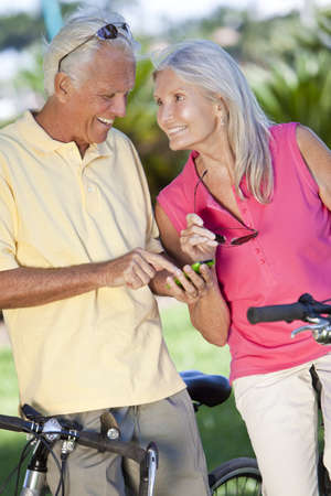 Happy senior man and woman couple cycling and together using a smart phone outside in sunshine photo