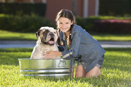 woman bath: A pretty young girl washing her her pet dog, a bulldog, outside in a metal bath tub