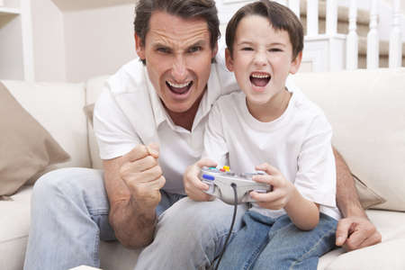 Happy man and boy, father and son, having fun playing video console games together, the young boy has the handset controller while dad is cheering. Stock Photo - 9436321